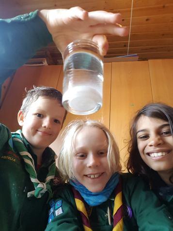 3 stolte drenge fremviser glas med vand